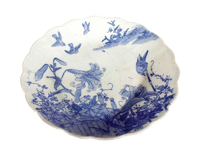 A blue and white plate with plants and birds decoration
